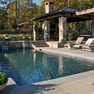 Design ideas for a medium sized rustic back rectangular swimming pool in Atlanta with a water feature and natural stone paving.