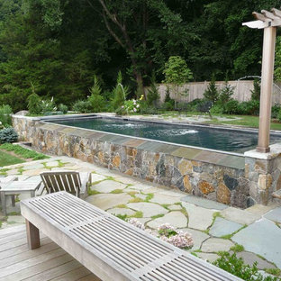 This is an example of a medium sized nautical back rectangular above ground swimming pool in Bridgeport with natural stone paving and a water feature.