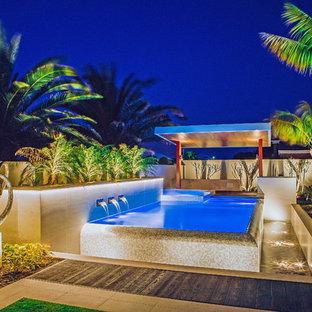 Modelo de piscina infinita, exótica, de tamaño medio, tipo riñón, en patio lateral, con suelo de baldosas