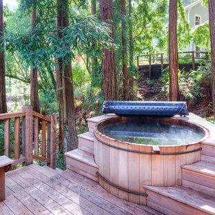 Immagine di una piscina stile rurale rotonda di medie dimensioni e dietro casa con una vasca idromassaggio e pedane