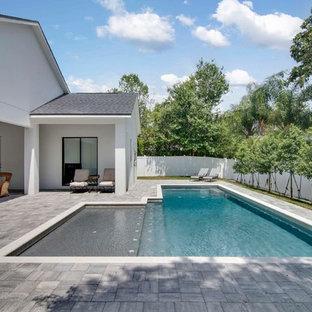 Diseño de piscina alargada, tradicional renovada, grande, rectangular, en patio trasero, con adoquines de hormigón