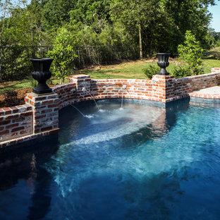Foto de piscina con fuente tradicional, grande, a medida, en patio trasero, con adoquines de ladrillo