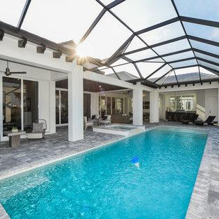 Idee per una grande piscina monocorsia tradizionale rettangolare dietro casa con pavimentazioni in pietra naturale