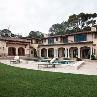 Großes Mediterranes Pool im Innehof in rechteckiger Form mit Poolhaus und Natursteinplatten in San Diego