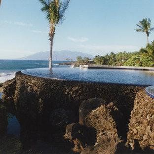 Foto de piscina con tobogán infinita, tropical, extra grande, redondeada, en patio trasero, con adoquines de piedra natural
