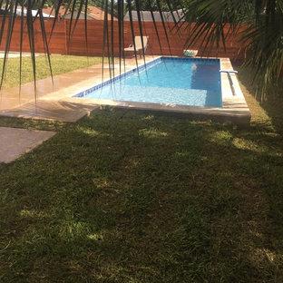 Foto de piscina con fuente alargada, actual, pequeña, rectangular, en patio trasero, con losas de hormigón