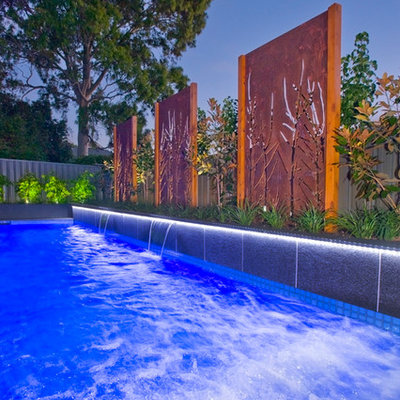 Inspiration for a mid-sized modern backyard stone and rectangular infinity pool remodel in Adelaide