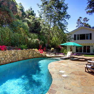 Example of a classic backyard stone and custom-shaped pool design in Los Angeles