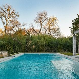 Ejemplo de piscina con fuente clásica renovada, grande, rectangular, en patio trasero, con granito descompuesto