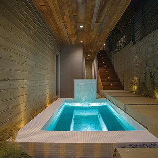 Foto de piscina con fuente natural, moderna, pequeña, rectangular, en patio lateral, con suelo de baldosas