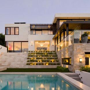 Foto di una piscina a sfioro infinito stile marino rettangolare di medie dimensioni e dietro casa con una vasca idromassaggio e pavimentazioni in cemento