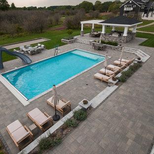 Diseño de casa de la piscina y piscina alargada, actual, grande, rectangular, en patio trasero, con adoquines de hormigón