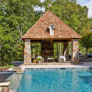Ispirazione per una grande piscina a sfioro infinito rettangolare dietro casa con fontane e pavimentazioni in pietra naturale