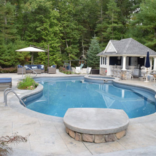 Inspiration for a mid-sized traditional backyard kidney-shaped lap pool in Providence with a pool house and stamped concrete.