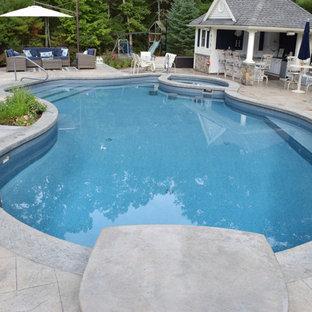 Imagen de casa de la piscina y piscina alargada, clásica, de tamaño medio, tipo riñón, en patio trasero, con suelo de hormigón estampado