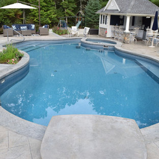 Photo of a mid-sized traditional backyard kidney-shaped lap pool in Providence with a pool house and stamped concrete.