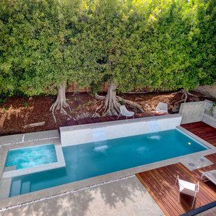 Пример оригинального дизайна: спортивный, прямоугольный бассейн среднего размера на заднем дворе в стиле модернизм с фонтаном и настилом