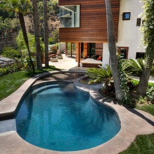 Esempio di una piscina minimal rotonda con lastre di cemento