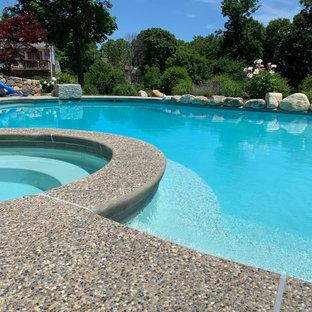 Esempio di un'ampia piscina naturale tradizionale personalizzata dietro casa con pedane