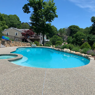 Expansive traditional backyard custom-shaped natural pool in Boston with with privacy feature and decking.