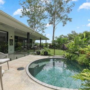 Ejemplo de piscina natural, asiática, pequeña, redondeada, en patio trasero, con suelo de hormigón estampado