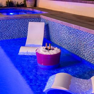 Exemple d'un grand couloir de nage arrière moderne rectangle avec un bain bouillonnant et du béton estampé.
