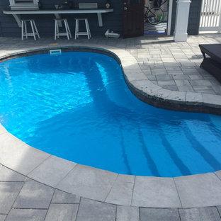 Foto de piscina alargada, clásica renovada, de tamaño medio, tipo riñón, en patio trasero, con adoquines de hormigón