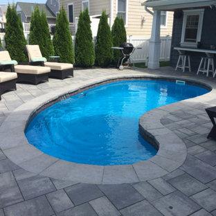 Ejemplo de piscina alargada, tradicional renovada, de tamaño medio, tipo riñón, en patio trasero, con adoquines de hormigón