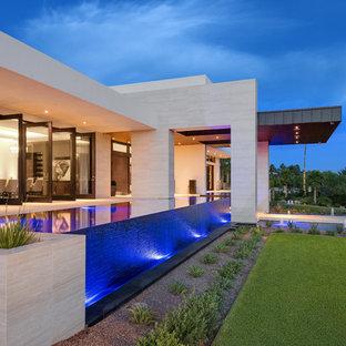 Réalisation d'une très grand piscine sur toit à débordement design sur mesure avec un point d'eau et du carrelage.