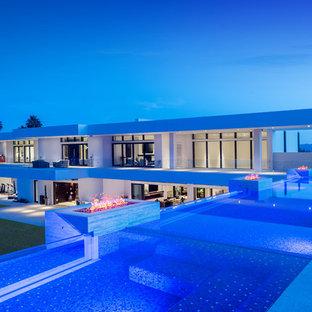 Foto di un'ampia piscina a sfioro infinito design personalizzata sul tetto con fontane e piastrelle