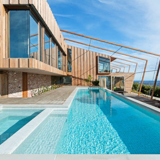 Photo of a contemporary l-shaped pool in Melbourne with a hot tub and decking.