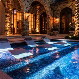 Foto de piscinas y jacuzzis alargados, mediterráneos, grandes, rectangulares, en patio trasero, con suelo de baldosas