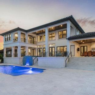 Ispirazione per una grande piscina naturale mediterranea personalizzata dietro casa con pavimentazioni in pietra naturale