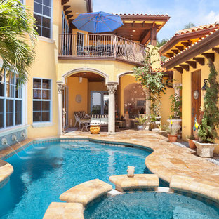 Example of a tuscan courtyard custom-shaped pool design in Charlotte