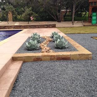 Diseño de piscina con fuente alargada, mediterránea, de tamaño medio, rectangular, en patio trasero, con suelo de baldosas