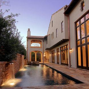 Mediterraner Pool hinter dem Haus in rechteckiger Form mit Wasserspiel in Houston