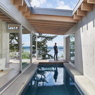 Imagen de piscina alargada, actual, extra grande, rectangular, en patio, con losas de hormigón