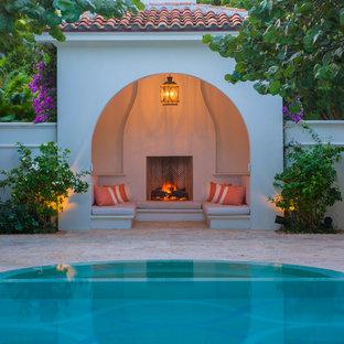 Geräumiger Mediterraner Pool in runder Form mit Poolhaus und Natursteinplatten in Miami