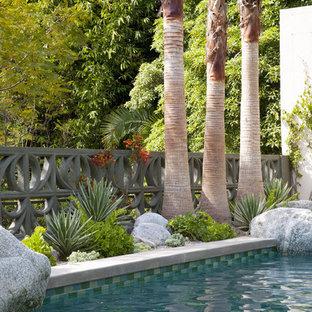 Ejemplo de piscina alargada, vintage, de tamaño medio, rectangular, en patio trasero, con adoquines de hormigón