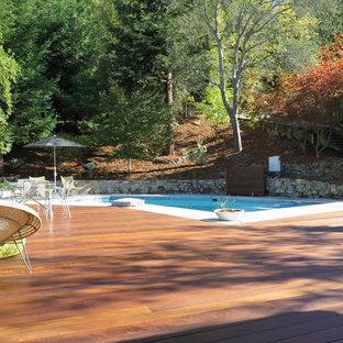 Diseño de piscina vintage, grande, a medida, en patio trasero, con entablado