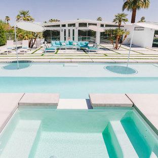 Ejemplo de piscinas y jacuzzis alargados, vintage, de tamaño medio, rectangulares, en patio trasero, con losas de hormigón