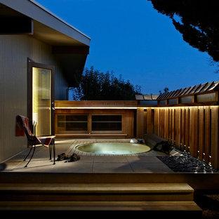 Diseño de piscinas y jacuzzis retro, extra grandes, redondeados, en patio trasero, con adoquines de hormigón