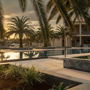 Esempio di una piscina a sfioro infinito moderna rettangolare dietro casa con pedane