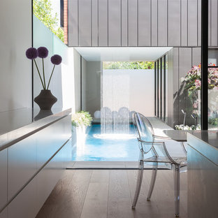 Diseño de piscina con fuente alargada, contemporánea, rectangular, en patio