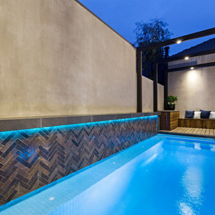 Photo of a small contemporary courtyard rectangular lap pool in Melbourne with a water feature.