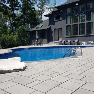 Foto de piscina natural, grande, a medida, en patio trasero, con adoquines de hormigón
