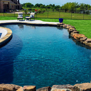 Inspiration for a large rustic backyard concrete and custom-shaped pool remodel in Dallas