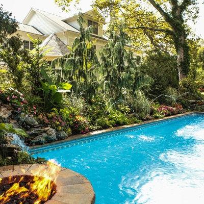 Large island style backyard stone and rectangular lap pool fountain photo in New York