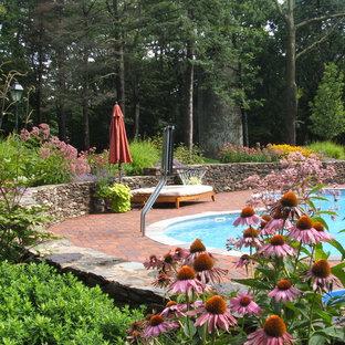 Imagen de piscina tradicional, tipo riñón, con adoquines de ladrillo