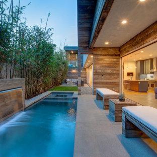 Ejemplo de piscina con fuente alargada, actual, de tamaño medio, rectangular, en patio trasero, con losas de hormigón